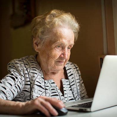 Anziana signora che siede al tavolo ed usa il suo computer
