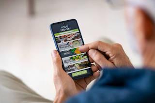 Anziano che utilizza il suo smartphone per ordinare cibo a casa