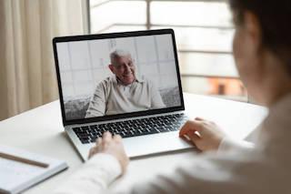 Giovane che effettua una videochiamata con il padre anziano