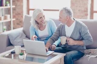 Due anziani guardano un film seduti sul divano utilizzando il loro computer